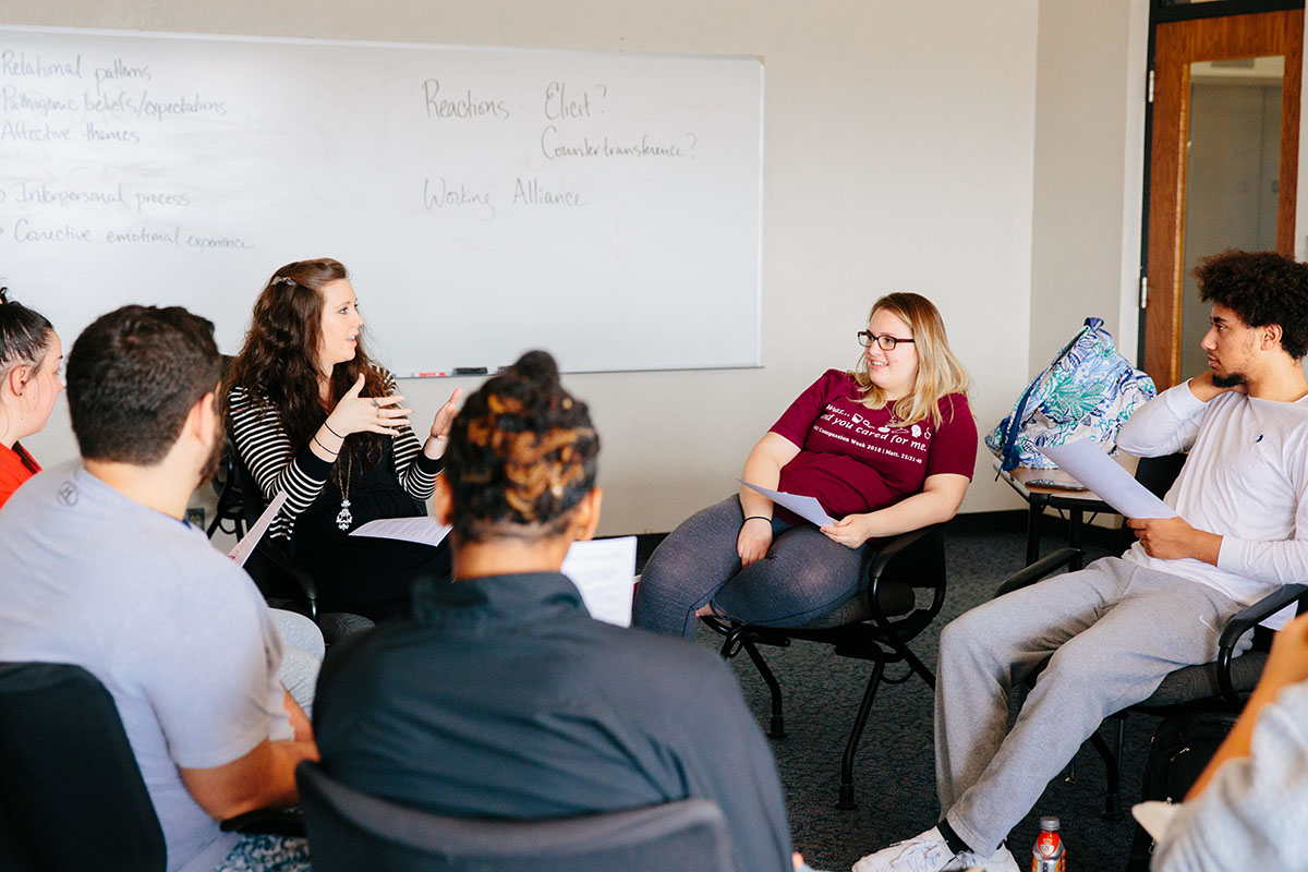 Students and professor discuss in classroom
