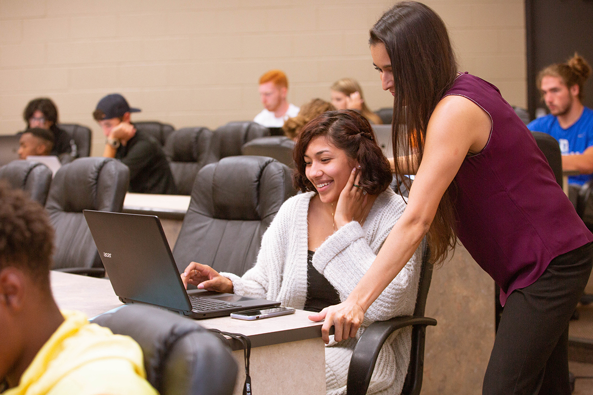 student working on computer with professor helping student