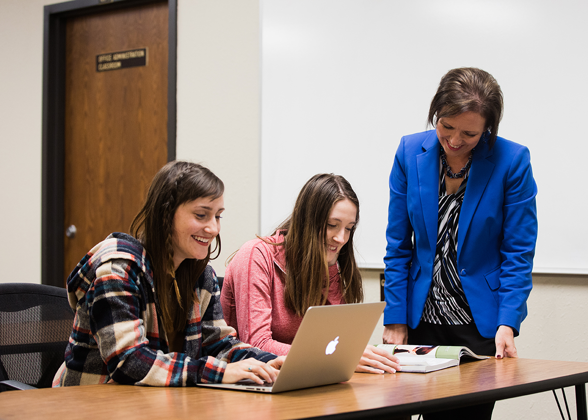 professor helping to female students in class